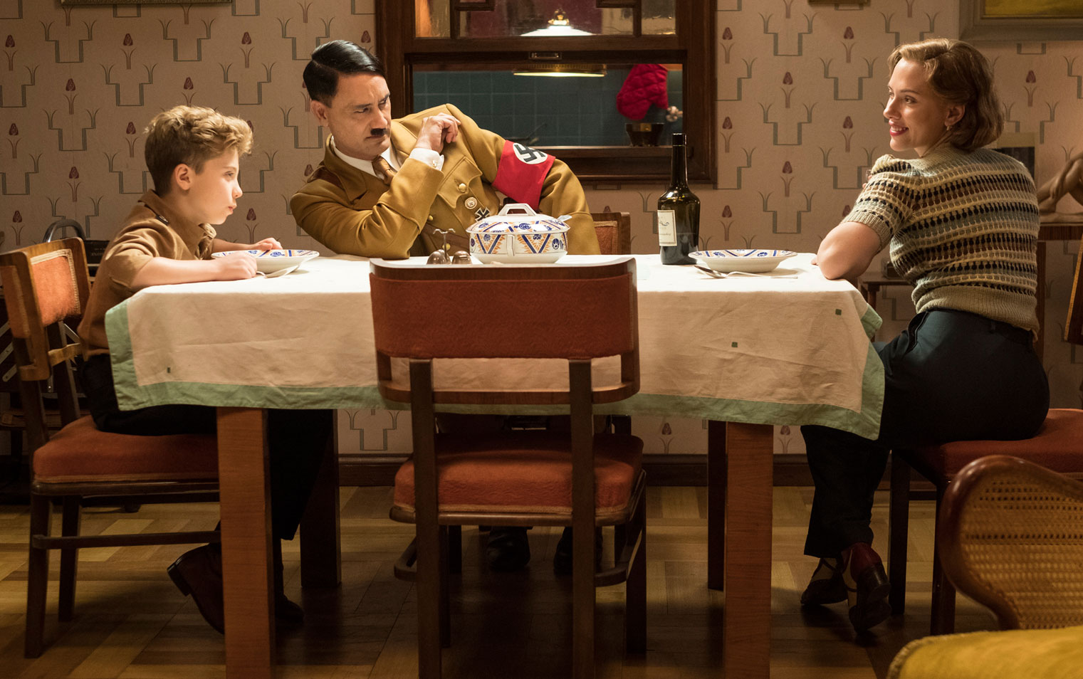 Film still of Jojo Rabbit dinner scene featuring Roman Griffin Davis,  Taika Waititi, and Scarlett Johansson