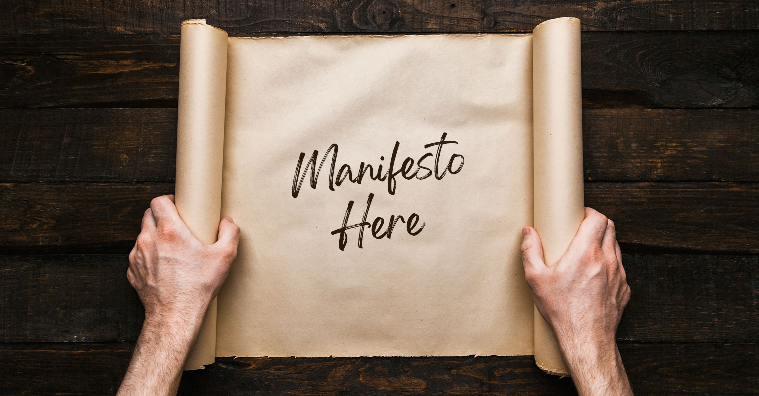 "Two hands unroll butcher paper with ""Manifesto Here"" handwritten on it"