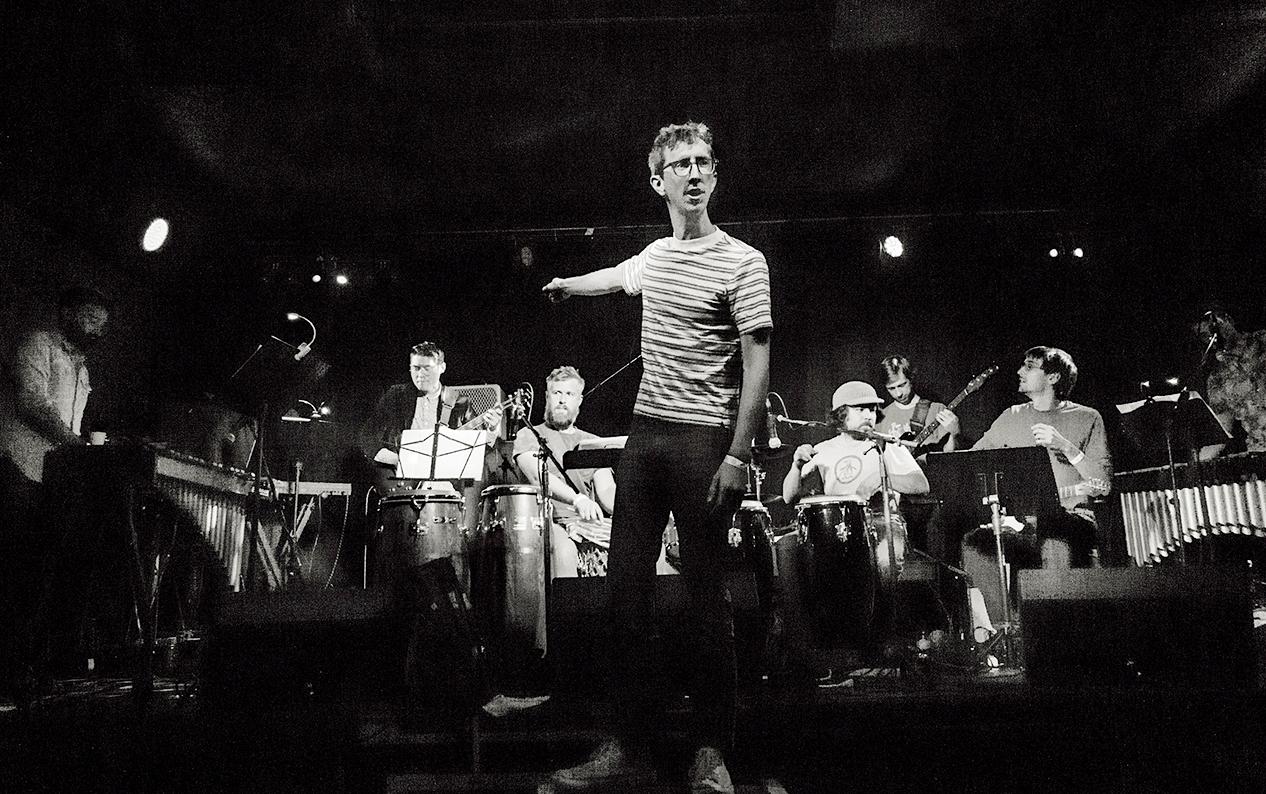 Black-and-white photo of Bay area-based musician Jordan Glenn instructing his band BEAK.