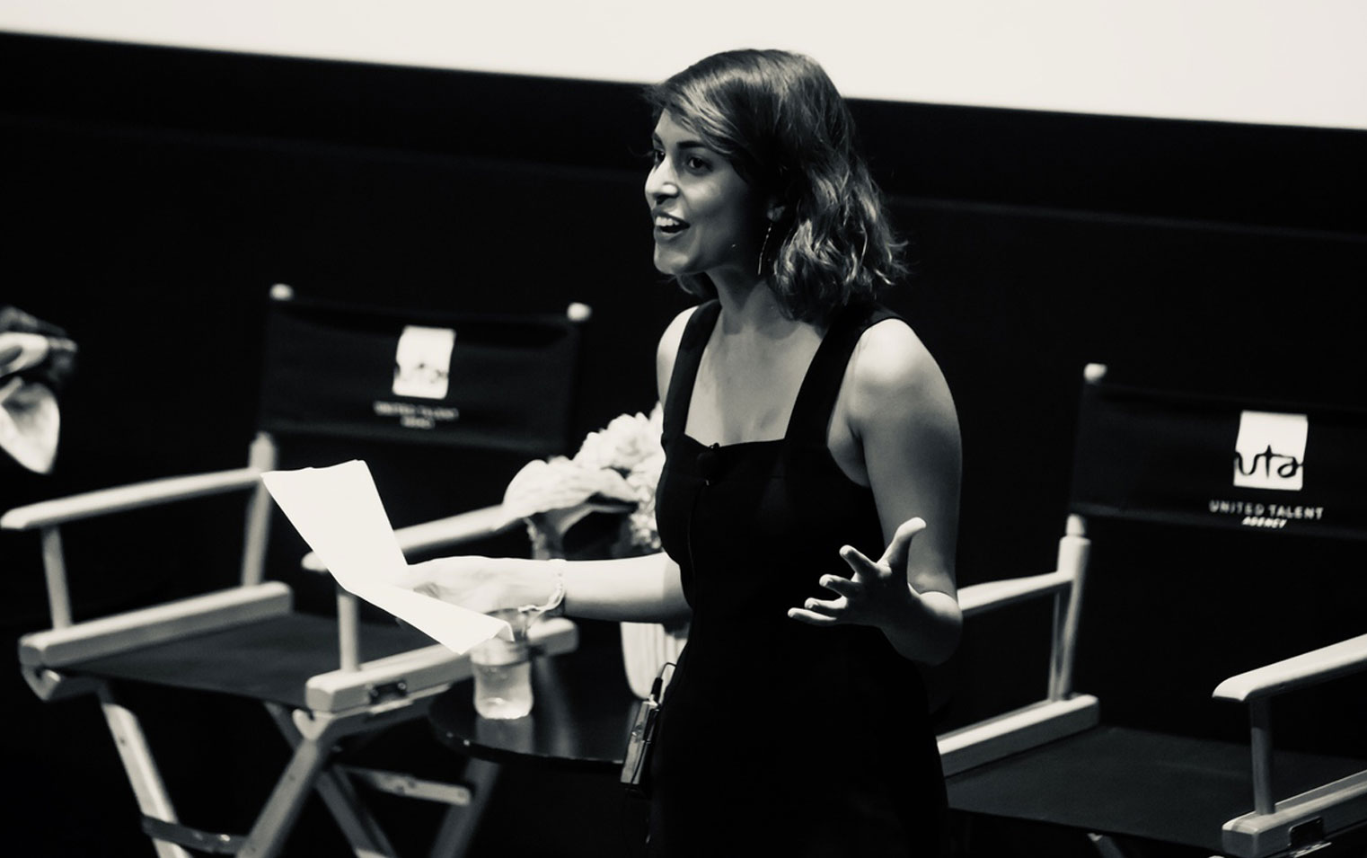 Black-and-white photo of podcast host, writer, and producer Misha Euceph moderating an event for the Secret Life of Muslims documentary series.