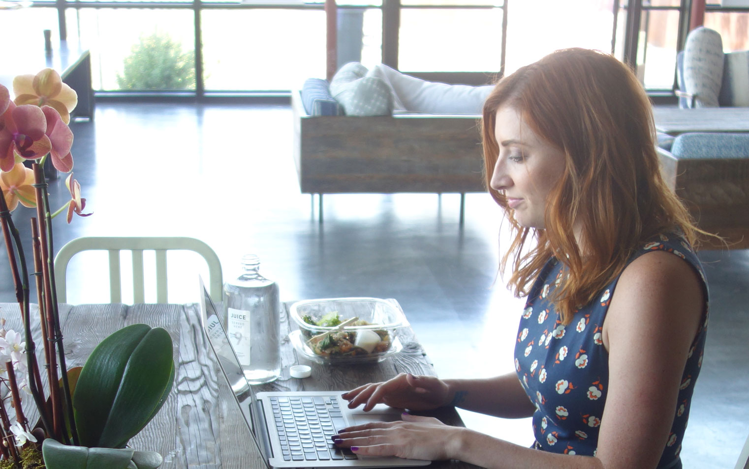 Rachael King, founder of Pod People, seated at table typing on open laptop.