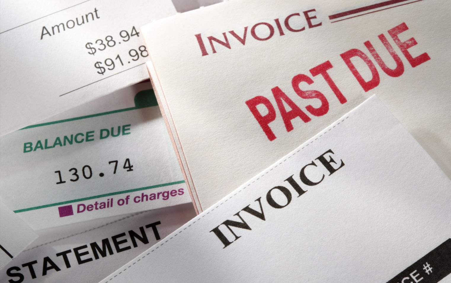 "Stack of papers with ""invoice,"" ""past due"" and ""balance due""due prominently displayed on each"