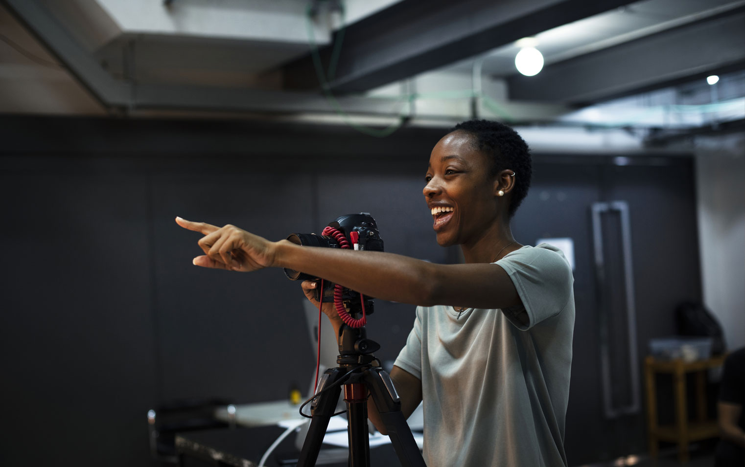 Smiling young African-American stands behind a camera on a tripod.